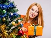 picture of merry chrismas  - Girl behind the Christmas tree with gift - JPG