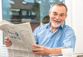stock photo of breakfast  - Happy senior man at breakfast with newspaper - JPG