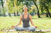 stock photo of crossed legs  - Young woman is listening music in the park and relaxing after exercise - JPG