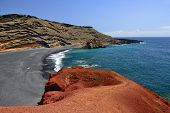 stock photo of canary-islands  - Lanzarote black sandy beach in gulf of El Golfo Atlantic ocean near Lago de los Clicos in Canary Islands - JPG