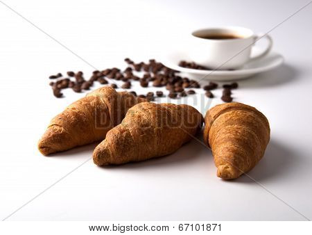Three Croissant And A Cup Of Coffee With Coffee Beans