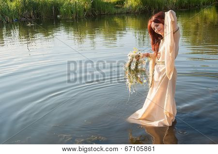 Beautiful red-haired girl relaxes in water