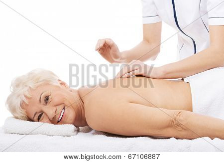 Old woman is having a massage. Spa concept.