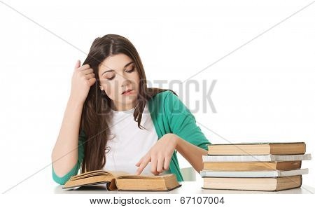 Teenage girl studying at the desk being tired