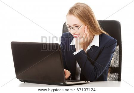Happy, cheerful caucasain business woman sitting by the table and looking at the screen laptop. Isolated on white.