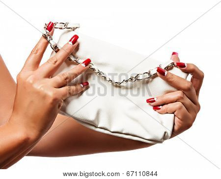 closeup of the woman�¢??s hand wearing red half moon nail art manicure with white leather bag with silver chain bag, isolated on white studio background