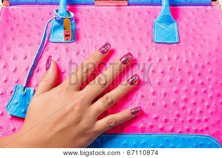 closeup of the woman's hand with bright art manicure, holding pink neon handbag with blue accents