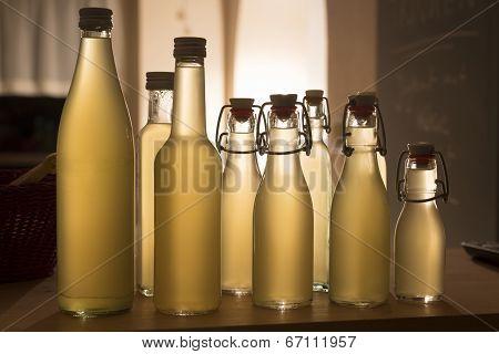 Bottles filled with elderflower syrup, shot against the light