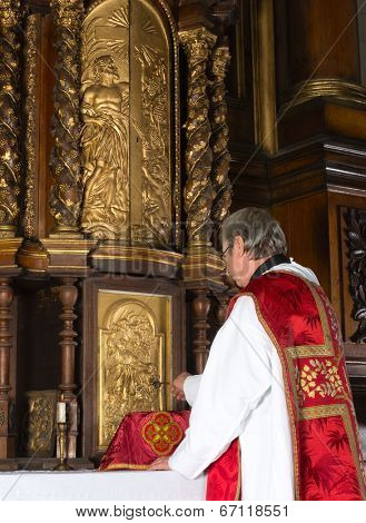 Priest opening the 17th century tabernacle in a medieval church with baroque interior