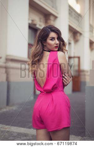 Fashion, Glamorous And Attractive Woman Dressed In A Sexy Sleeveless, Backless Pink Jumpsuit. Elegan