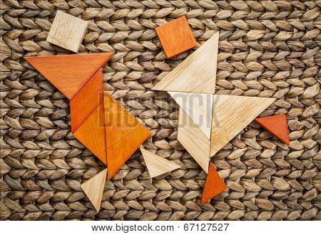 a couple of dancers or martial artists - abstract figures  built from tangram wooden pieces, a traditional Chinese puzzle game, against oven water hyacinth mat,  artwork created by the photographer