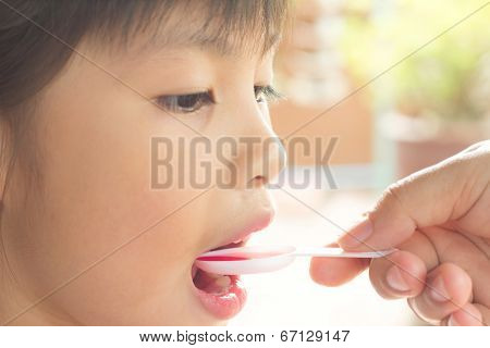 Giving A Spoon Of Syrup To Little Girl