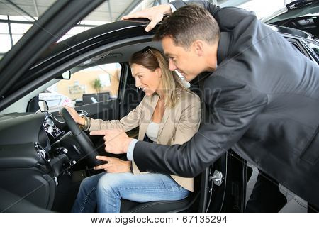 Car dealer showing vehicle to woman