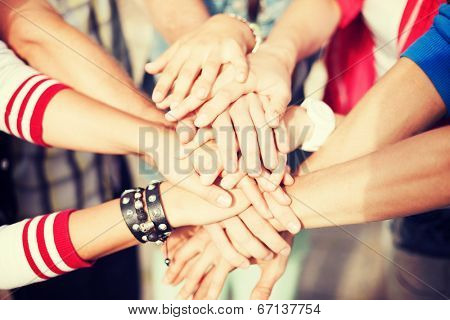 success and gesture concept - close up of teenagers hands on top of each other outdoors
