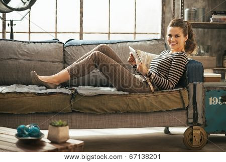 Smiling Young Woman Laying On Divan And Using Tablet Pc In Loft Apartment