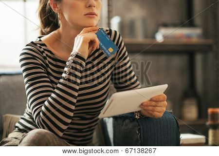 Closeup On Thoughtful Young Woman With Credit Card And Tablet Pc
