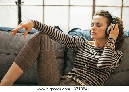 Young Woman Listening Music In Headphones While Sitting On Couch