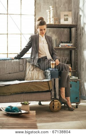 Full Length Portrait Of Business Woman With Coffee Latte Sitting On Divan In Loft Apartment