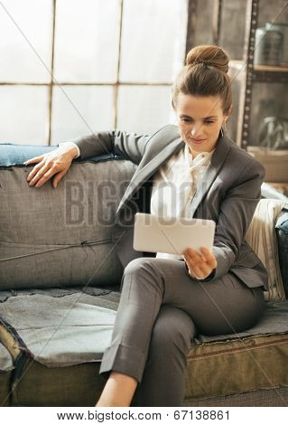 Business Woman Sitting On Divan In Loft Apartment And Using Tabl