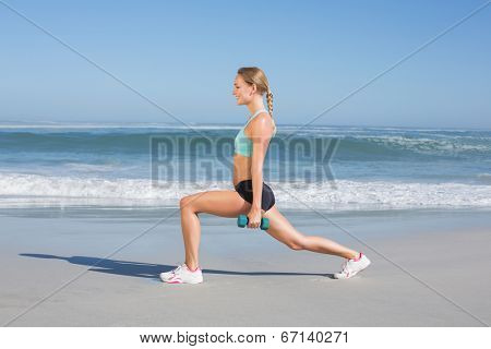 Fit woman doing weighted lunges on the beach on a sunny day