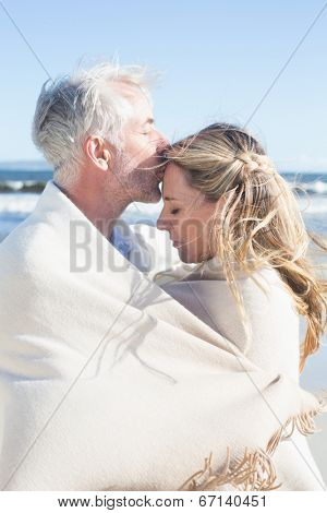 Affectionate couple wrapped up in blanket on the beach on a sunny day