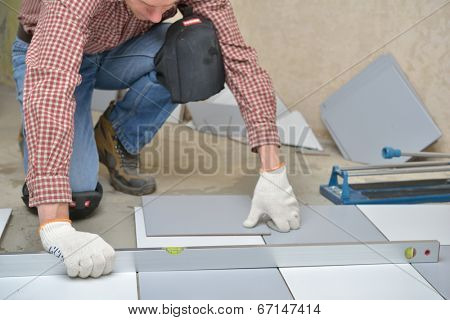 Tiler installs ceramic tiles on a floor