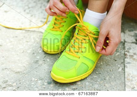 Young woman tying shoelace outside