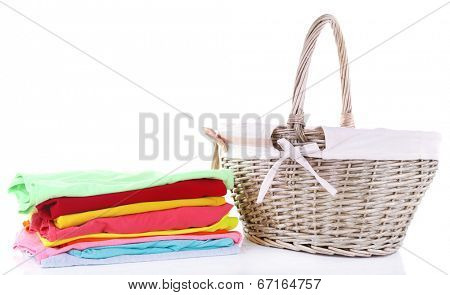Bright clothes and empty wicker basket, isolated on white