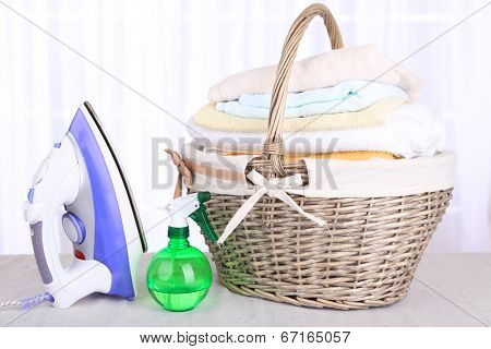Colorful towels in basket, iron on light background