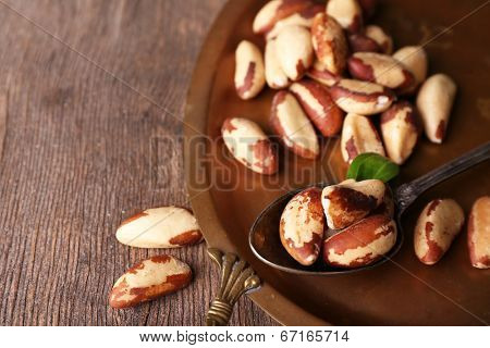Tasty brasil nuts on salver, on wooden background
