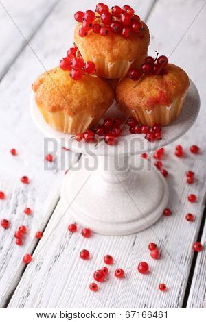 Tasty muffin with red currant berries on color wooden background