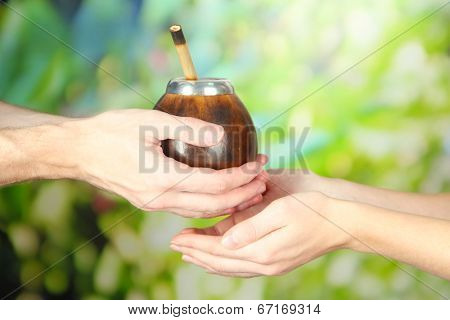 Man hands giving calabash and bombilla with yerba mate, on nature background