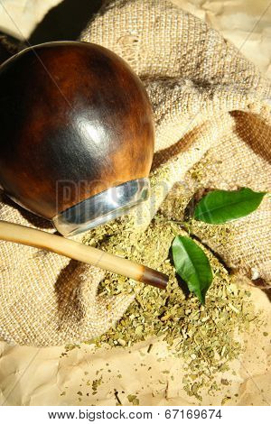 Calabash and bombilla with yerba mate on burlap background