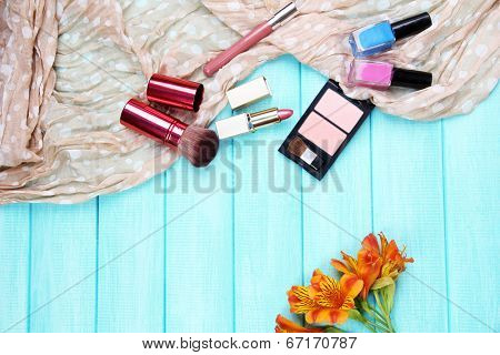 Eyeshadow, brushes, lipstick and flowers on color wooden background