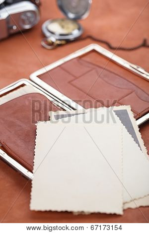 vintage photographs with  old wallet, watch and camera on leather table, retro colors