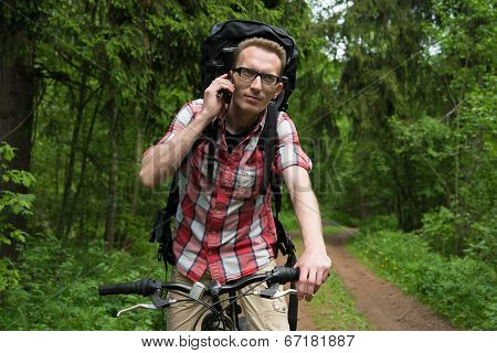 Young Man With Bicycle Talking In The Forest On Mobile Phone.