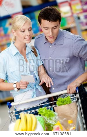 Couple discussing the shopping list and chosen products standing near the shopping trolley full of food