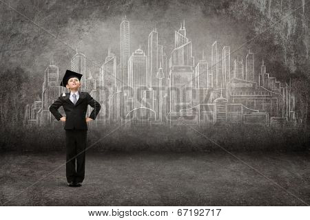 Full-length portrait of little student with hands on hips against modern city drawing. Concept of graduation and dreams