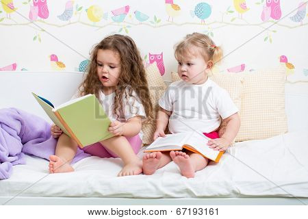 Kids Sisters Reading A Book In Bed
