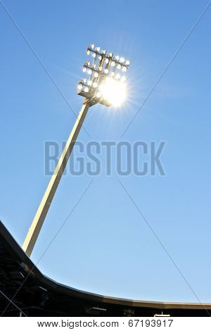 Stadium lights at dusk against a blue sky with the lights on