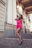 foto of jumpsuits  - Fashion glamorous and attractive woman dressed in a sexy sleeveless pink jumpsuit posing in full body length with long legs - JPG