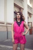 pic of jumpsuits  - Fashion glamorous and attractive woman dressed in a sexy sleeveless pink jumpsuit with a hand in her hair - JPG