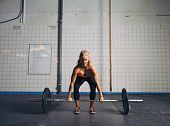 foto of gym workout  - Strong young woman lifting heavy weights at gym - JPG