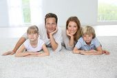 pic of carpet  - Happy family of four laying on carpet at home - JPG