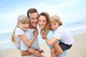 stock photo of piggyback ride  - Parents giving piggyback ride to kids at the beach - JPG