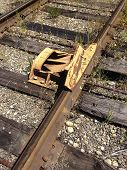 image of railroad car  - A train car derailment device is attached to railroad tracks to keep drifting cars from rolling and causing damage by derailing the car off the tracks - JPG
