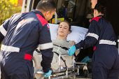 stock photo of stretcher  - paramedics taking unconscious patient into an ambulance - JPG