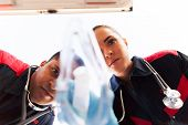 stock photo of paramedic  - low angle view of paramedics putting oxygen mask on patient - JPG