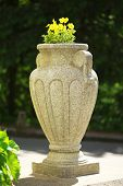 stock photo of planters  - Stone planter with flowers near driveway of house - JPG
