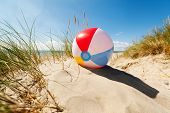 foto of children beach  - Beach ball resting in sand dune concept for childhood summer vacations - JPG